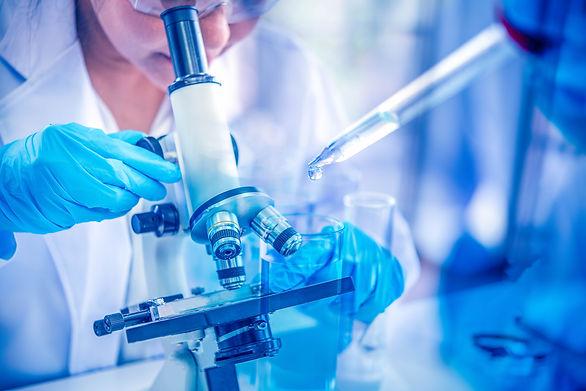 Women scientist looking through microsco
