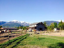 barn and horse pens in front of mountains