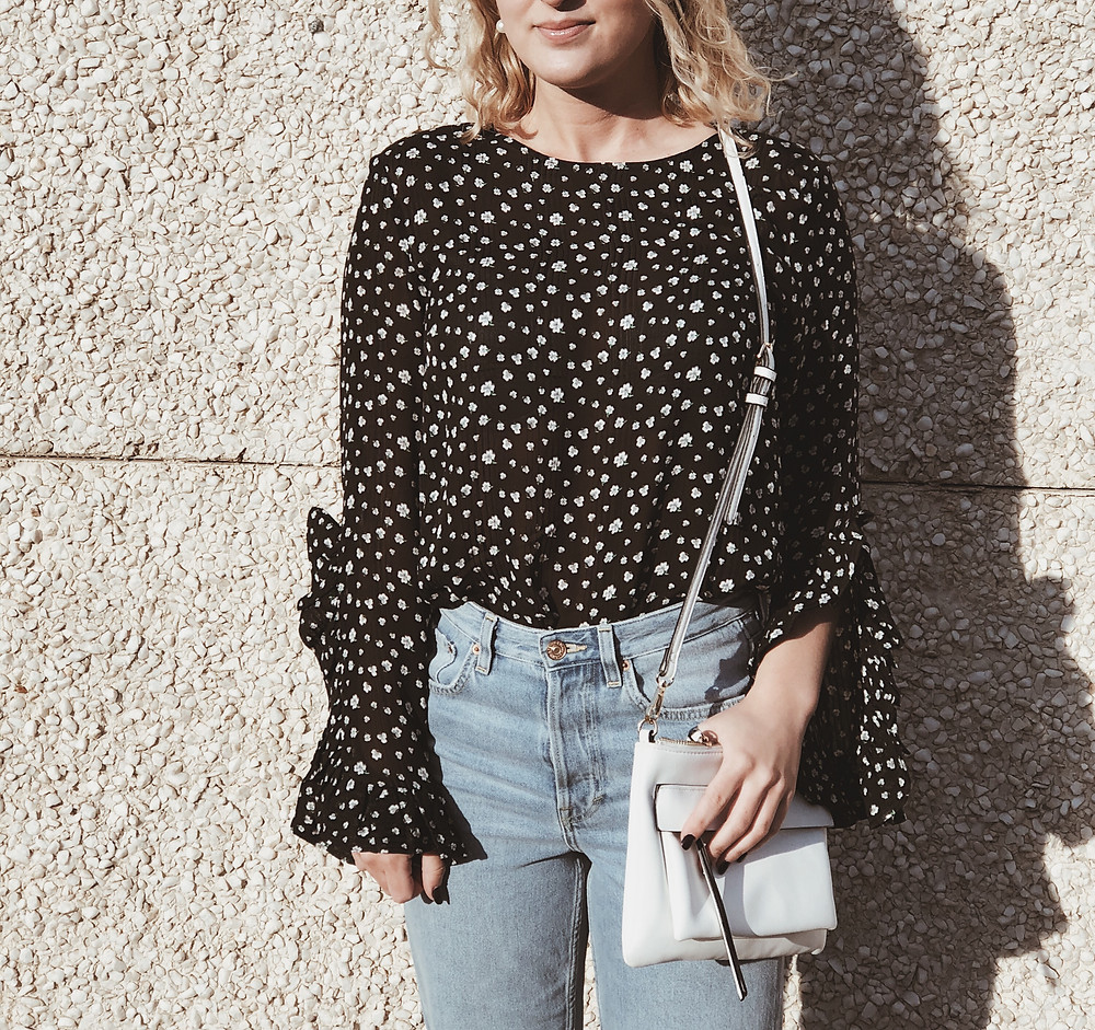 Dark floral print top with flounce sleeves paired with straight cut denim jeans