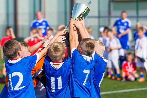 Young Soccer Players Holding Trophy. Boy