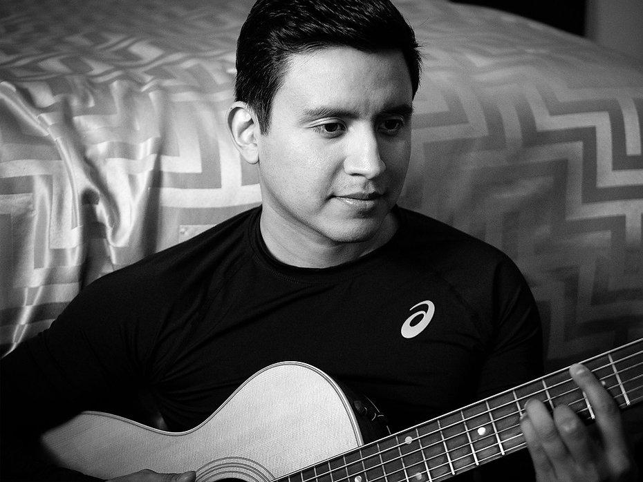 Photo of Joe Steven playing acoustic guitar