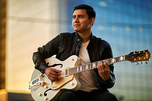 Joe Steven wearing leather jacket holding electric guitar