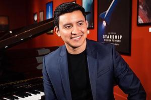 Joe Steven wearing blue suit sitting next to grand piano