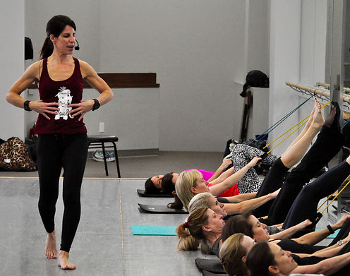 This group class in New Canaan is doing floor work during a Pilates and barre fusion class, using resistance bands.