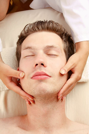 A female hands massaging man's face in a