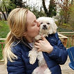 woman kissing small white senior dog who is in hospice care