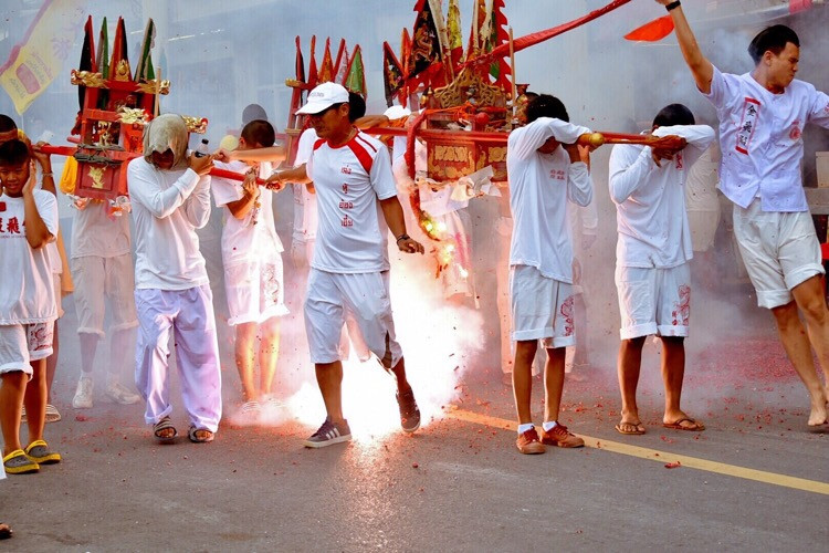 30 Sep. - Kamala, Phuket, Thailand - Fire crackers are thrown on the open palanquin and can fall on the devotees who are carrying them. © jerraleen balais