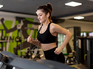 side-view-female-running-treadmill_23-21