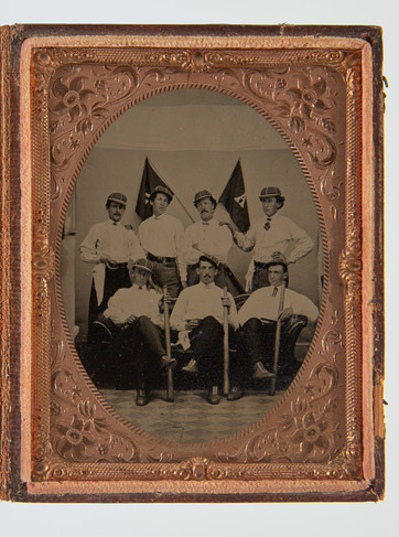 """Fine tintype of a baseball team. 3 team members are holding bats in the front row. of the 4 members in the back row, one holds a baseball. Crossed flags with insignia  A in the background. Original case. 19th century. H 4-7/8, W 3-11/16""""."""