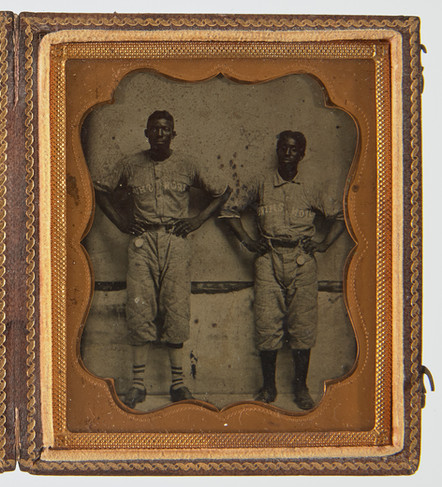 """Tintype of two Afro-American baseball players sporting pocket watches. Written on jerseys, IRONSHIRE. Probably Ironshire, Maryland. Original case. 19th century. H 3-3/4"""", W 3-1/4""""."""