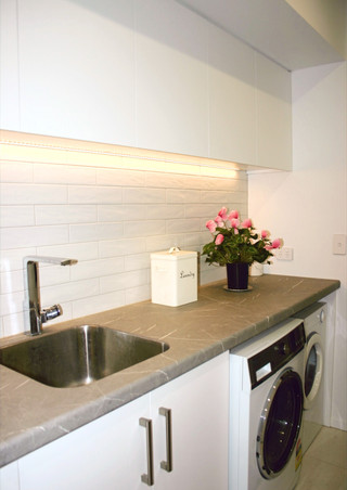 Laundry room with storage cupboards and task lighting