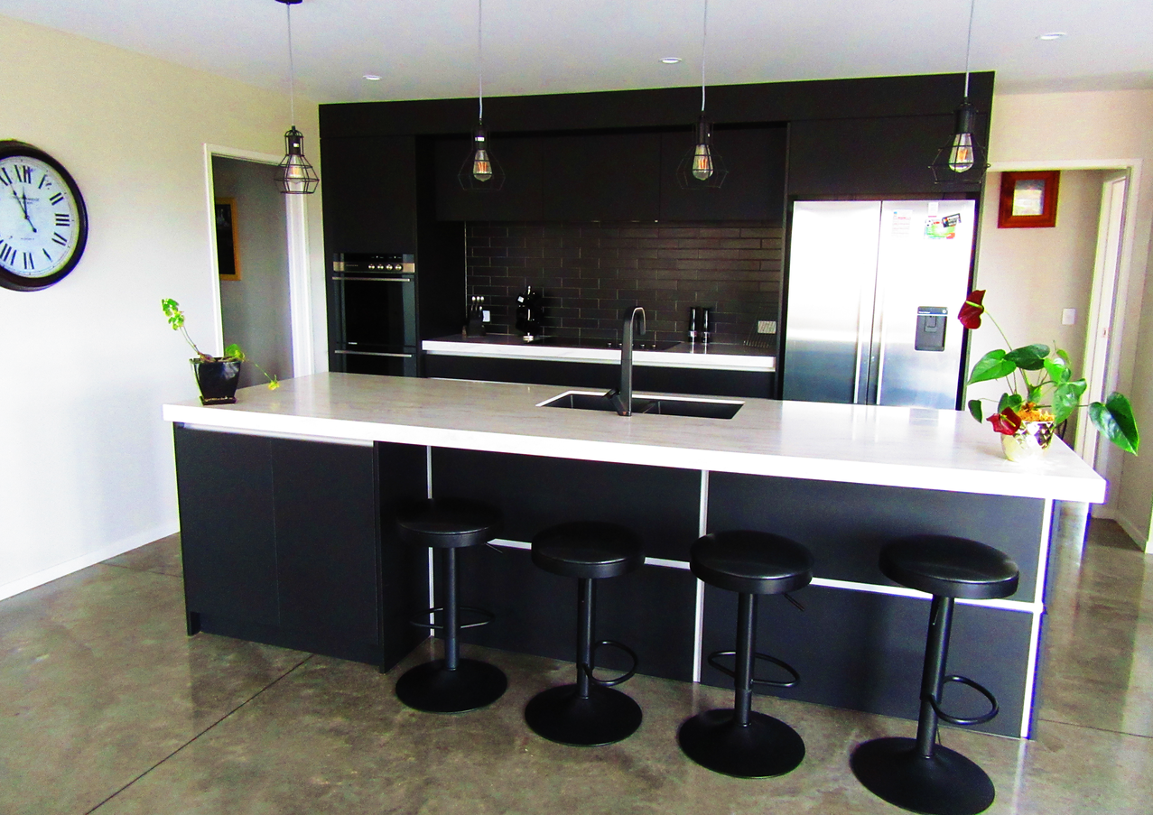 Modern black kitchen with corian benchtop from In House Kitchens