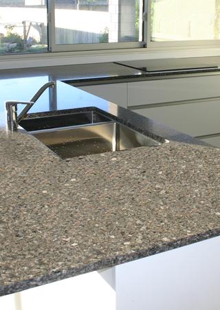 Engineered stone kitchen bench in streamlined handleless kitchen