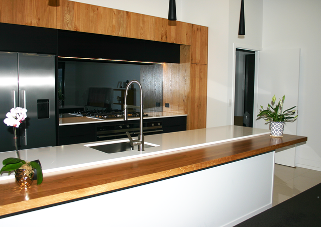 Black and white kitchen with mirrored splashback and timber accents