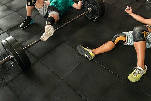 two-men-lying-on-gym-floor-beside-black-