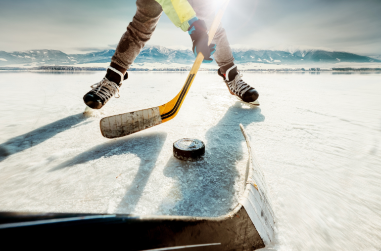 quebec-adult-hockey-leagues-prohibited-players-long-for-the-game-hockey-players-face-off-over-puck-on-ice-with-mountain-as-backdrop