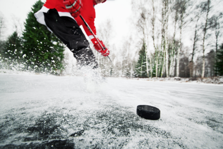 quebec-adult-hockey-leagues-prohibited-players-long-for-the-game-hockey-player-in-bright-red-uniform-has-puck-on-ice-with-forest-as-background