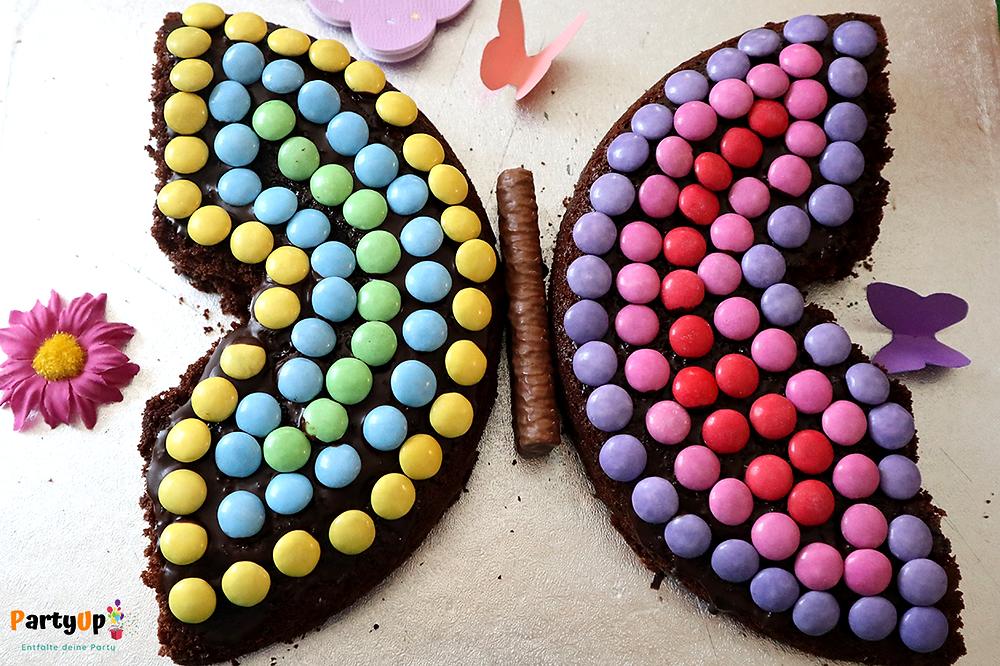 Schmetterling Kuchen aus Schokolinsen und Schokoladenkuchen für den Kindergeburtstag