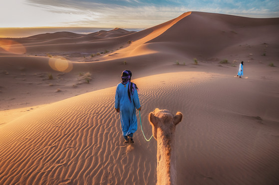 Two Tuareg nomads leading a camel in the