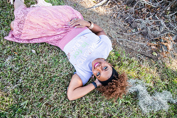 Validation is for Fly lying in the grass rocking her Validation is for Parking tee by Kee's Tees; image take by Davillier Photograpy.