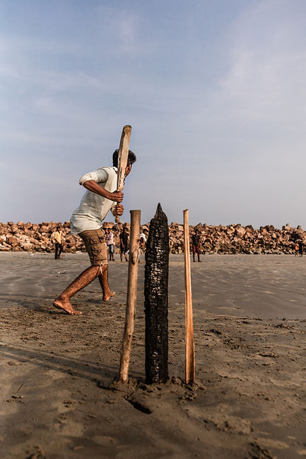 Kid playing cricket on beach in India. Walking Wicket