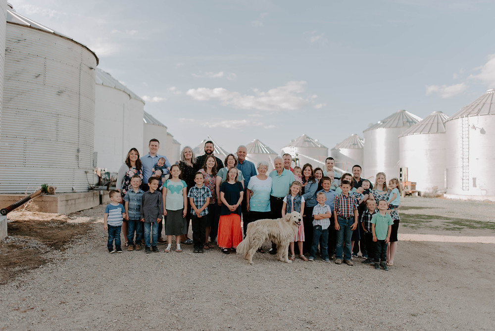 The family who runs Amish Family Popcorn in front of silos on their farm