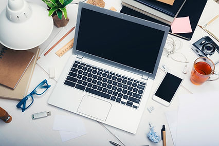 laptop with desk supplies around it