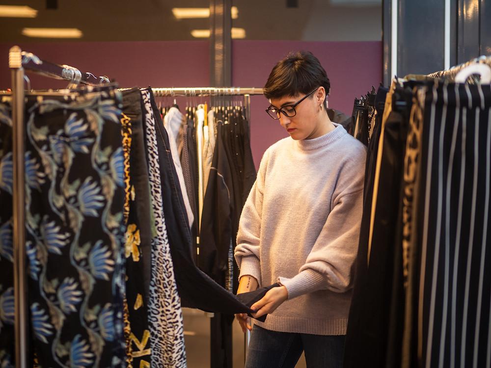 En kvinna med glasögon och beige tröja som känner på ett plagg i en garderob.
