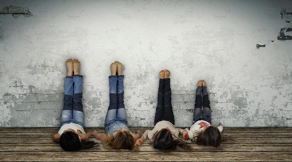 Fyra barn som ligger med benen upp mot en vägg för att visa upp lagade jeans.