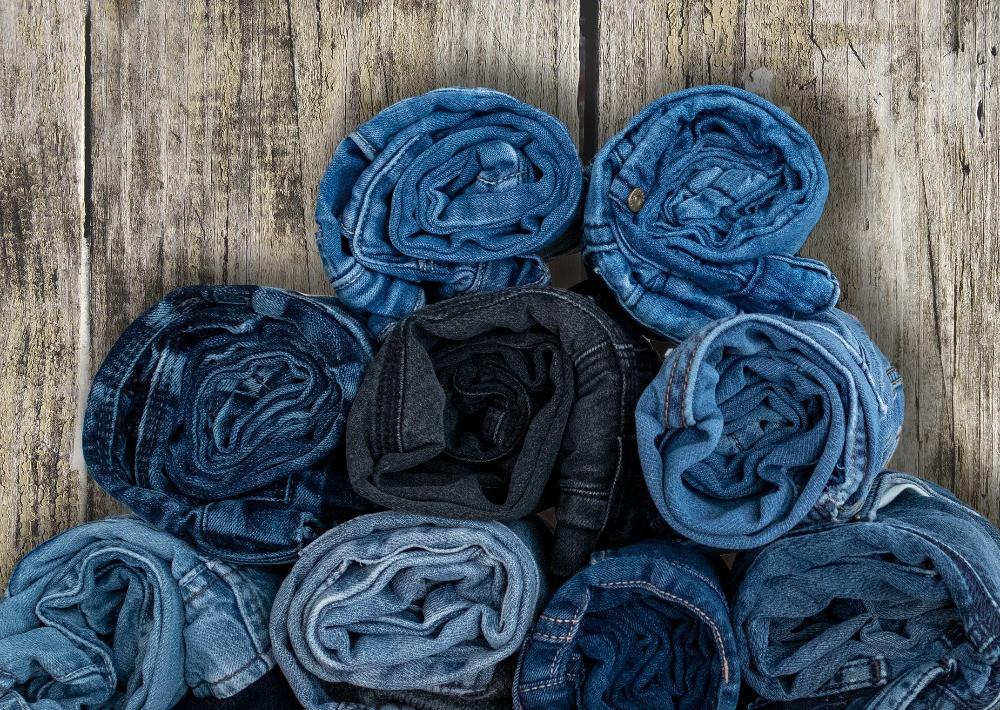 Flera par hoprullade jeans för barn på en bakgrund av trä.