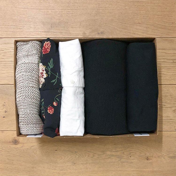 Kläder vikta i en låda på ett golv.