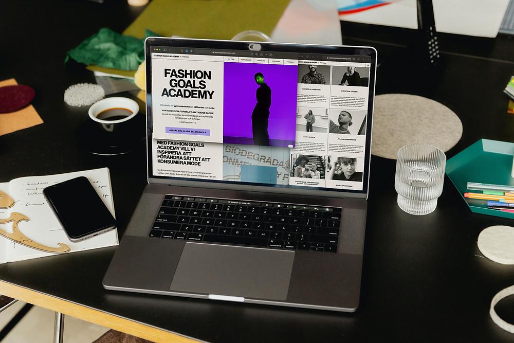 Skrivbord med en laptop på som visar Popswaps projekt Fashion Goals Academy.
