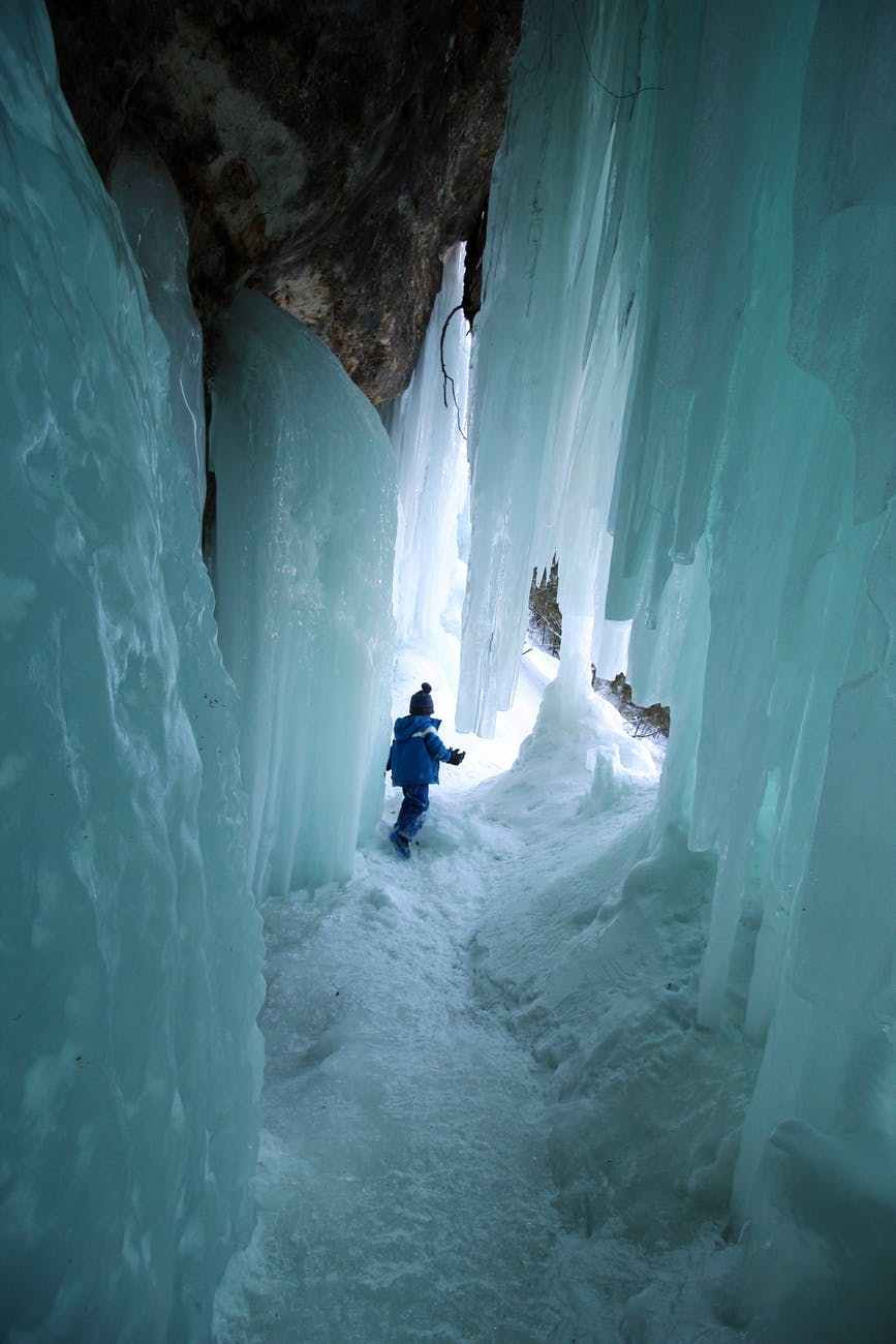 kid playing in a cave with snow
