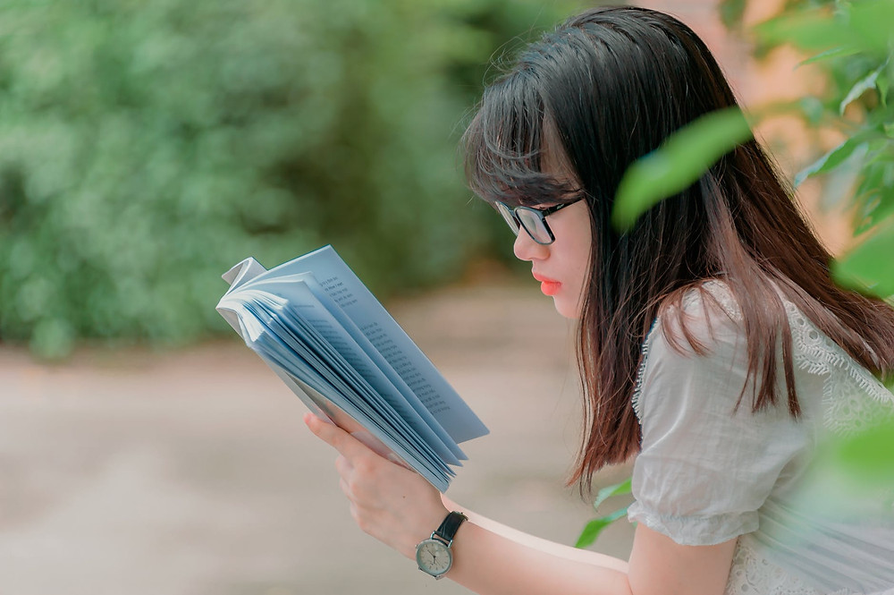 close up photography of girl reading book