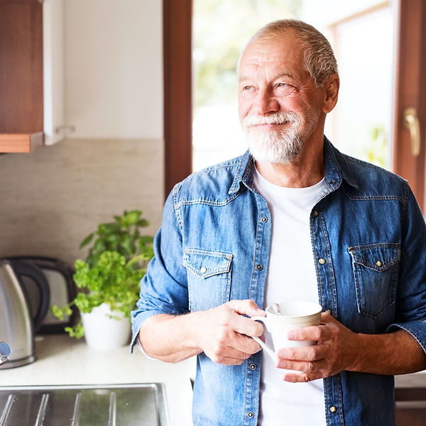 Happy senior man holding a cup of coffee