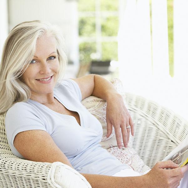 Senior Woman Sitting Outside Reading Mag