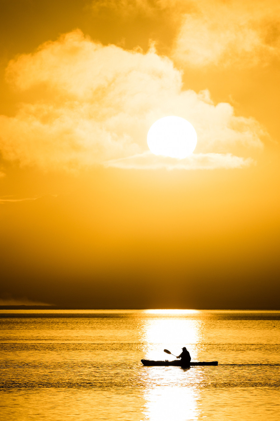 Der perfekte Augenblick: Kajak auf ruhiger See in Island im Strahl der untergehenden Sonne.