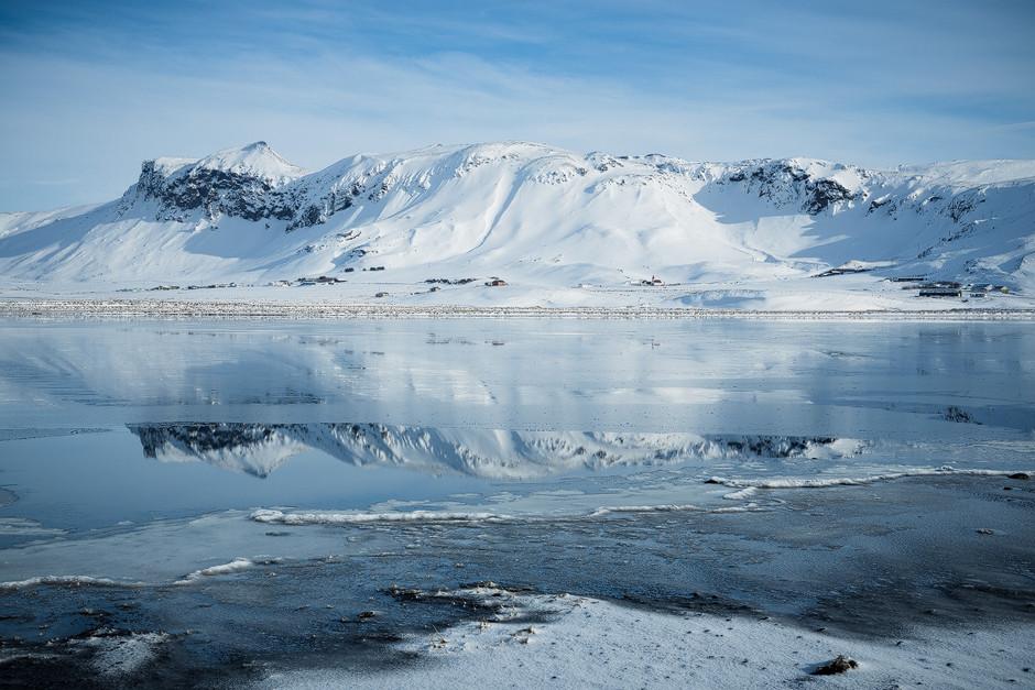 Gespiegeltes Bergpanorama auf Island: Wow - hier zu wohnen, in dieser epischen Kulisse, muss herrlich sein. Wenn das raue Wetter nicht wäre.