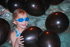 A young girl with blue goggles swims in a pool with black balloons