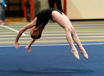 A young girl in a black leotard is in the middle of a back handspring on a blue floor