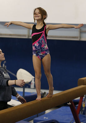 Young girl standing on a balance beam with a smile on her face