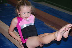 Young girl in a pink leotard sitting on a balance beam in a V-Sit during gymnastics class