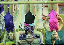 Three young girls in leotards hang upside down by their knees while laughing.