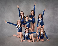 Seven girls in matching blue and white leotards pose for a formal competitive gymnastics photo