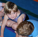 Preschool aged girl wearing a leotard, crouched down in a squat, participating in a gymnastics class