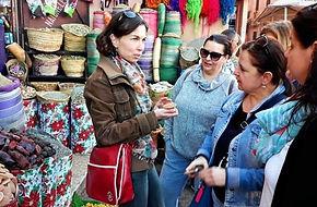 Tereza Huclova s cervenou taskou a tri ucastnice zajezdu pred kosiky s marockym korenim
