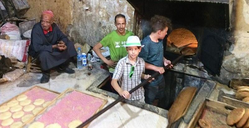 Dva chlapci si zkouší upéct chléb tradičním marockým způsobem.