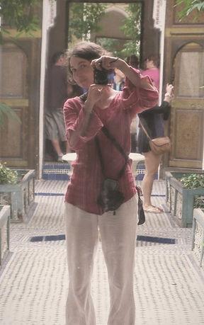 Tereza Huclova v bilych volnych kalhotech, volne cervene halene s fotoaparatem pred marockymi stukovanymi dvermi