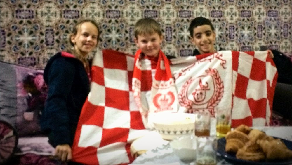 Marocký chlapec ukazuje českým dětem fotbalovou vlajku.