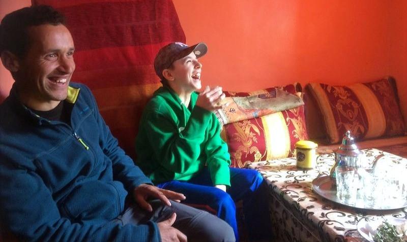 Marocký průvodce vysvětluje smějícímu se chlapci, jak pít marocký čaj.